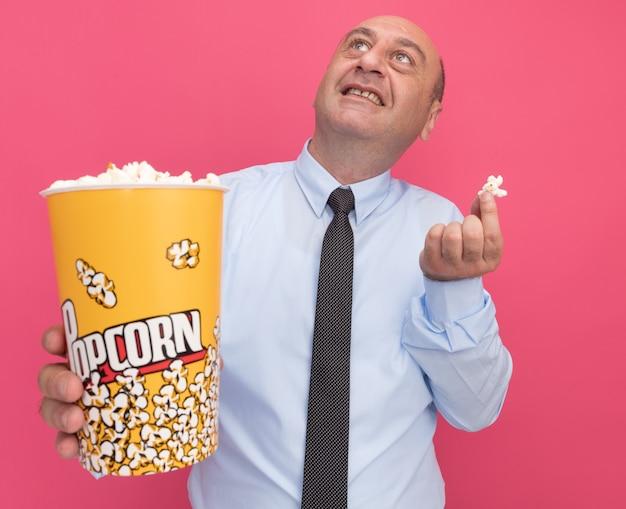 Uśmiechnięty mężczyzna w średnim wieku, ubrany w białą koszulkę z krawatem, trzymający wiadro popcornu z kawałkiem popcornu na różowej ścianie