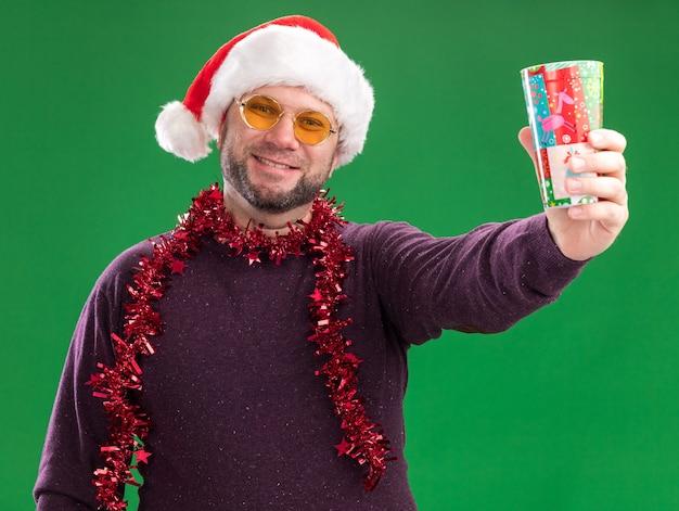 Uśmiechnięty mężczyzna w średnim wieku ubrany w czapkę mikołaja i świecącą girlandę na szyi z okularami wyciągającymi plastikowy świąteczny kubek odizolowany na zielonej ścianie