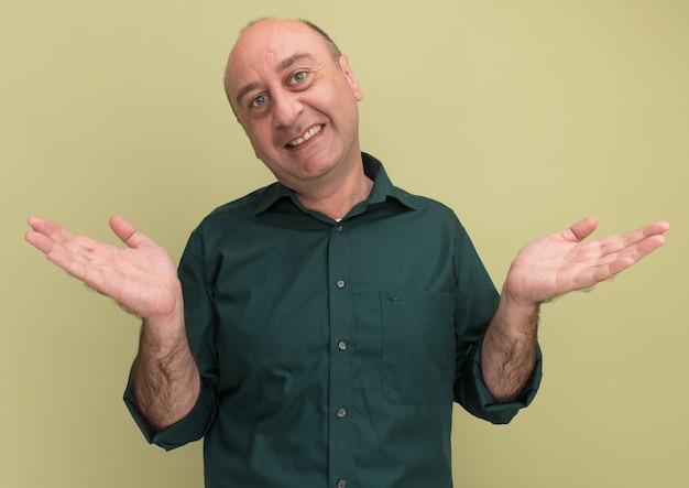 Uśmiechnięty mężczyzna w średnim wieku ubrany w zieloną koszulkę rozkładającą ręce na oliwkowo-zielonej ścianie