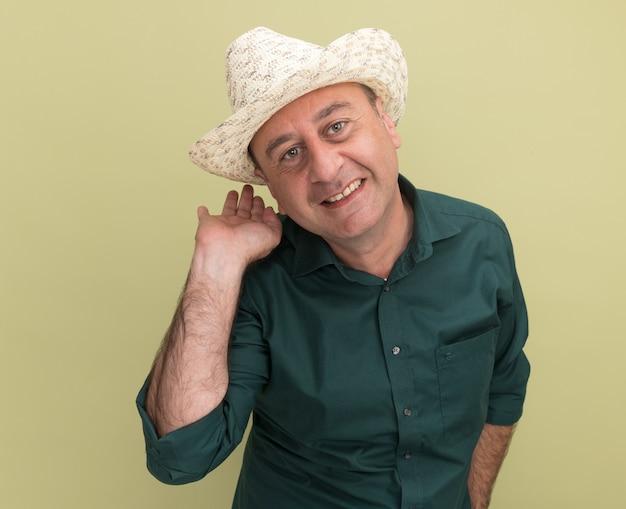 Uśmiechnięty mężczyzna w średnim wieku ubrany w zielony t-shirt i kapelusz punkty za na białym tle na oliwkowej ścianie z miejsca na kopię