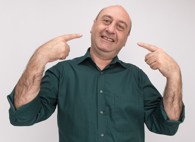 Uśmiechnięty mężczyzna w średnim wieku ubrany w zielony t-shirt wskazuje na siebie na białym tle na białej ścianie