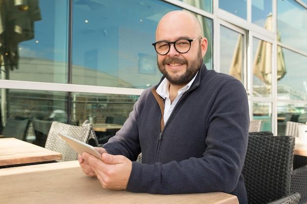 Uśmiechnięty mężczyzna w średnim wieku używa pastylkę w ulicznej kawiarni