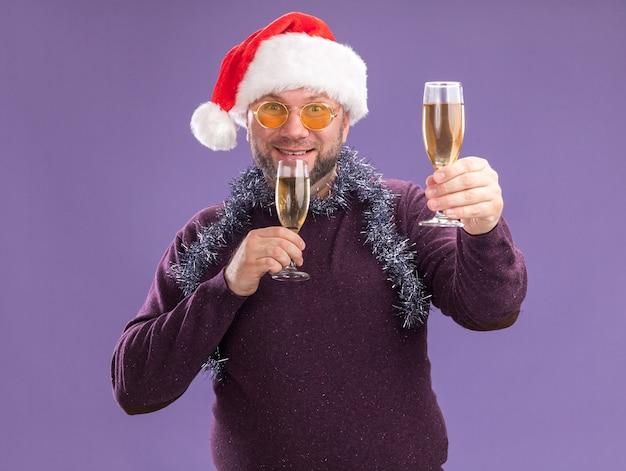Uśmiechnięty mężczyzna w średnim wieku w czapce mikołaja i girlandzie świecidełka na szyi z okularami trzymającymi dwie szklanki szampana wyciągniętą jedną na fioletowej ścianie