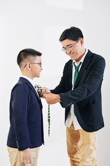 Uśmiechnięty mężczyzna w średnim wieku z azji pomaga synowi dopasować krawat, przygotowując się do świętowania