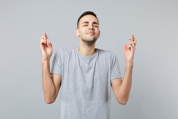 Uśmiechnięty mężczyzna w zwykłych ubraniach czeka na wyjątkowy moment, trzymając kciuki, zamknięte oczy, życząc