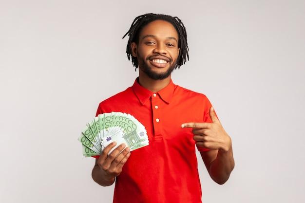 Uśmiechnięty mężczyzna wskazując palcem na gotówkę euro w ręku, patrząc na kamery, dobre wynagrodzenie, płatności.