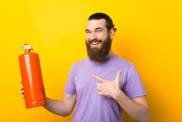 Uśmiechnięty mężczyzna wskazuje na czerwoną gaśnicę na żółtym tle.