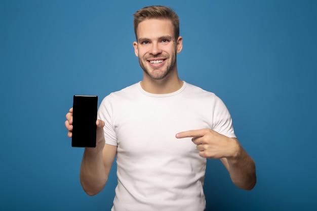 Uśmiechnięty mężczyzna wskazuje z palcem przy smartphone odizolowywającym na błękicie