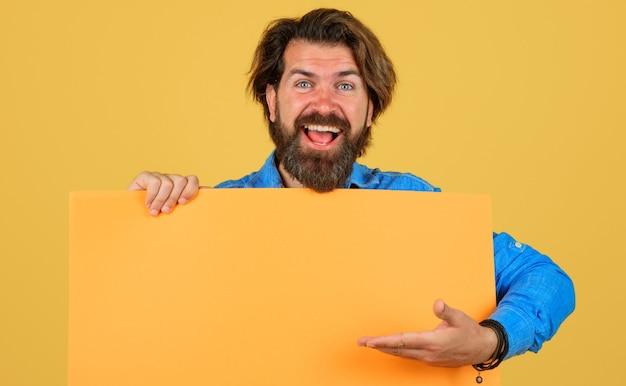 Uśmiechnięty mężczyzna z banerem reklamowym. brodaty mężczyzna z pustą tablicą znak. miejsce na tekst. reklama. czarny piątek. sprzedaż i rabat. wyprzedaże sezonowe.