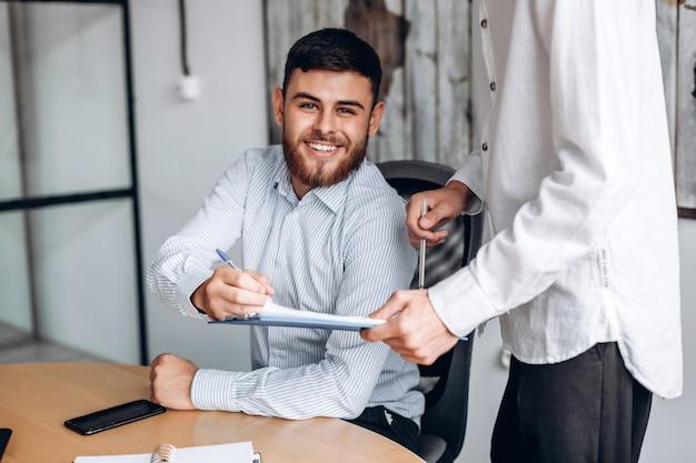 Uśmiechnięty mężczyzna z brodą, pracuje w biurze, przegląda ważne dokumenty i podpisuje je