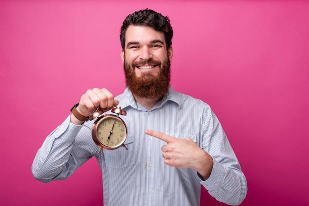 Uśmiechnięty mężczyzna z brodą w swobodnym wskazaniu na budzik