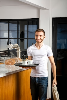 Uśmiechnięty mężczyzna z dwoma filiżankami kawy na tacy