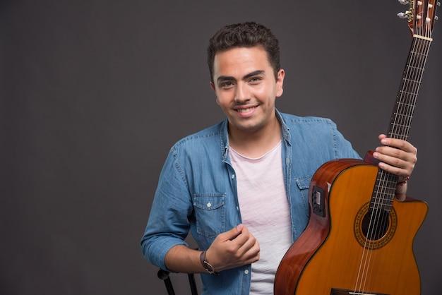 Uśmiechnięty mężczyzna z gitarą uśmiecha się na ciemnym tle.
