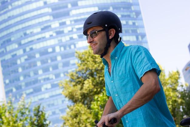 Uśmiechnięty mężczyzna z kaskiem jeżdżący na rowerze po mieście w słoneczny dzień alternatywne dojazdy do pracy w obszarze uban z panoramą na tle
