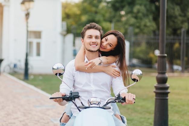 Uśmiechnięty mężczyzna z krótką fryzurą jadący skuterem w dół zielonej ulicy, podczas gdy jego długowłosy przyjaciel go przytula