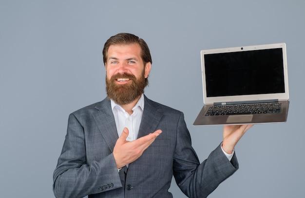 Uśmiechnięty mężczyzna z laptopem w biurze biznesowy mężczyzna z komputerem w miejscu pracy technologia