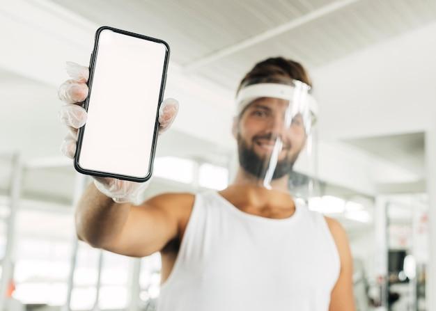 Uśmiechnięty mężczyzna z osłoną twarzy na siłowni, trzymając smartfon