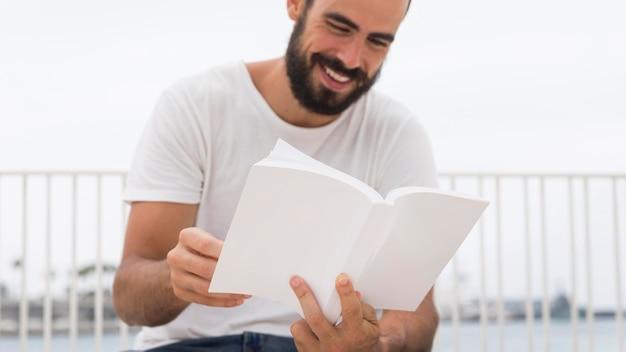 Uśmiechnięty mężczyzna z paciorkami czytanie książki na zewnątrz