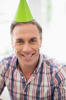 Uśmiechnięty mężczyzna z partyjnym kapeluszem w domu