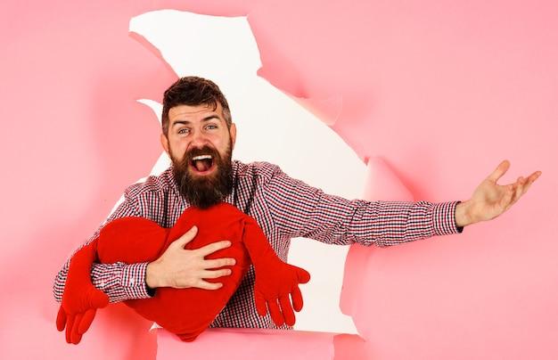 Uśmiechnięty mężczyzna z poduszką w kształcie serca. brodaty facet z czerwoną poduszką w kształcie serca. symbol miłości. koncepcja walentynki.