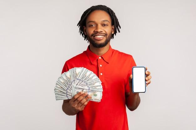 Uśmiechnięty mężczyzna z pozytywnym wyrazem twarzy mężczyzna trzymający telefon komórkowy i dużo pieniędzy,