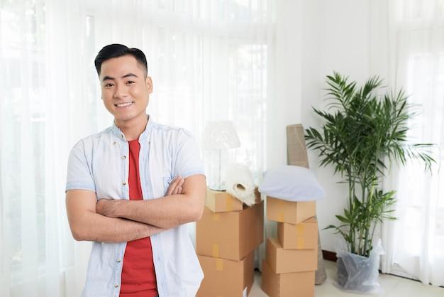 Uśmiechnięty mężczyzna z rękami skrzyżowanymi w nowym mieszkaniu