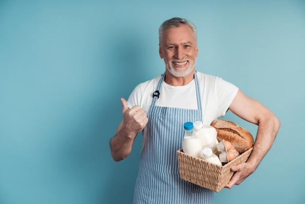 Uśmiechnięty mężczyzna z siwymi włosami i brodą trzyma kosz z jedzeniem i wskazuje kciukiem na miejsce