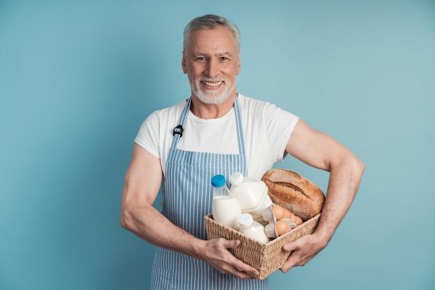 Uśmiechnięty mężczyzna z siwymi włosami i brodą, trzymając kosz z jedzeniem