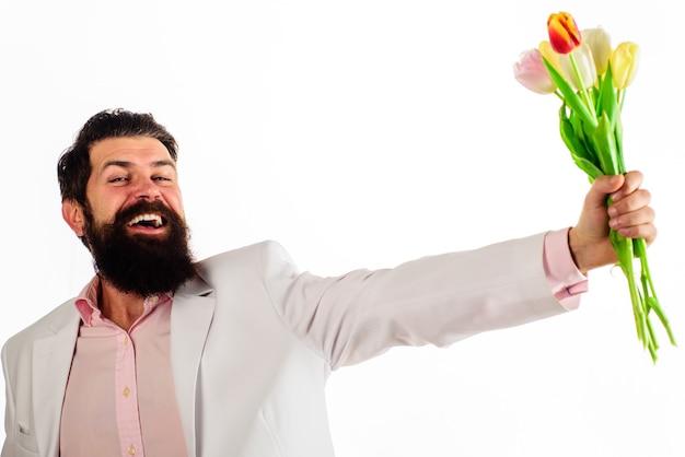 Uśmiechnięty mężczyzna z tulipanami. brodaty mężczyzna z bukietem kwiatów. walentynki, dzień kobiet, obchody urodzin.