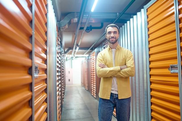 Uśmiechnięty mężczyzna z założonymi rękami w piwnicy