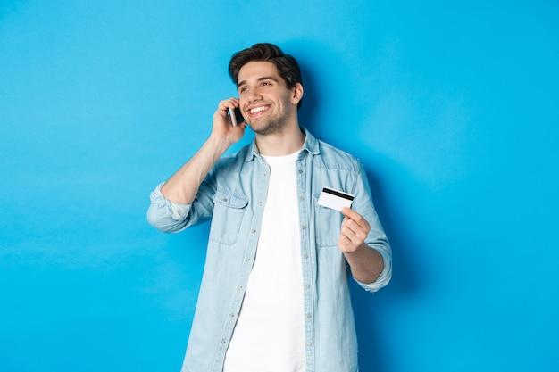 Uśmiechnięty mężczyzna zadzwoń do banku wsparcia, rozmawia przez telefon komórkowy i trzyma kartę kredytową, stojąc przed niebieską ścianą
