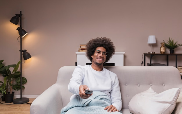 Uśmiechnięty mężczyzna zmienia kanały telewizyjne