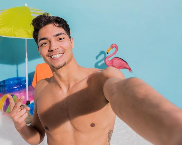 Uśmiechnięty mięśniowy facet na plaży bierze selfie