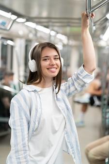 Uśmiechnięty milenijny pasażer słodkiej dziewczyny słuchający muzyki za pomocą bezprzewodowych słuchawek w pociągu metra
