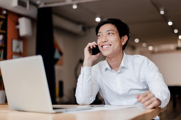Uśmiechnięty millenial azjatykci biznesmen opowiada na telefonie w firmy biurze z laptopem