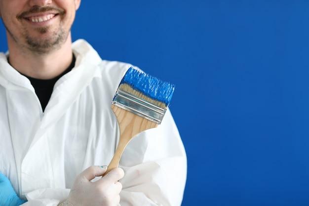 Uśmiechnięty mistrz malarz pokojowy trzyma pędzel z niebieską farbą