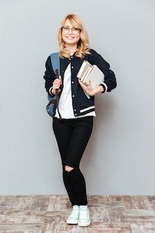 Uśmiechnięty młoda kobieta uczeń jest ubranym szkła z plecakiem