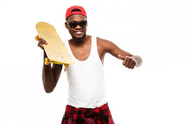 Uśmiechnięty młodego człowieka mienia deskorolka i seans aprobaty