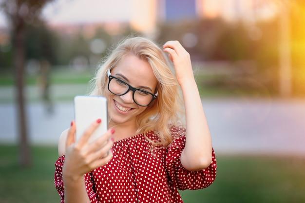 Uśmiechnięty młodej kobiety blogger w szkłach z telefonem w lato parku