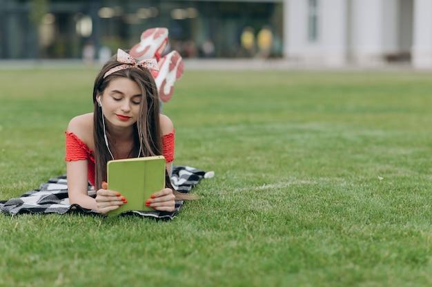 Uśmiechnięty młodej kobiety lying on the beach na zielonej łące i słuchanie muzyka przez hełmofonów. kobieta, słuchanie muzyki