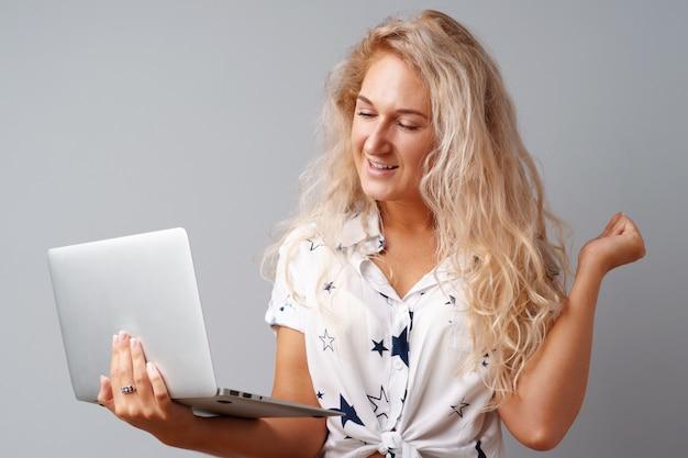 Uśmiechnięty młodej kobiety mienia laptop