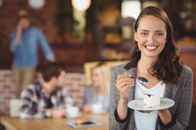 Uśmiechnięty młodej kobiety mienia tort