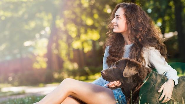 Uśmiechnięty młodej kobiety obsiadanie z jej psem w ogródzie