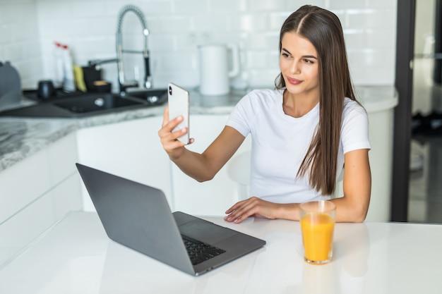 Uśmiechnięty młodej kobiety wideo dzwoni na telefonie w kuchni
