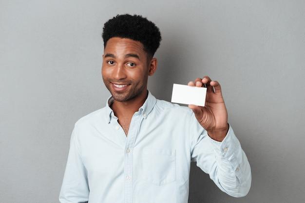 Uśmiechnięty młody afro amerykański facet trzyma pustą wizytówkę