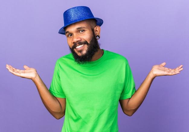 Uśmiechnięty młody afro-amerykański facet w imprezowym kapeluszu rozkładającym dłonie na niebieskiej ścianie