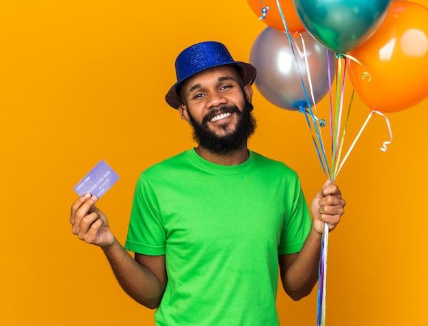 Uśmiechnięty młody afro-amerykański facet w imprezowym kapeluszu, trzymający balony i kartę kredytową