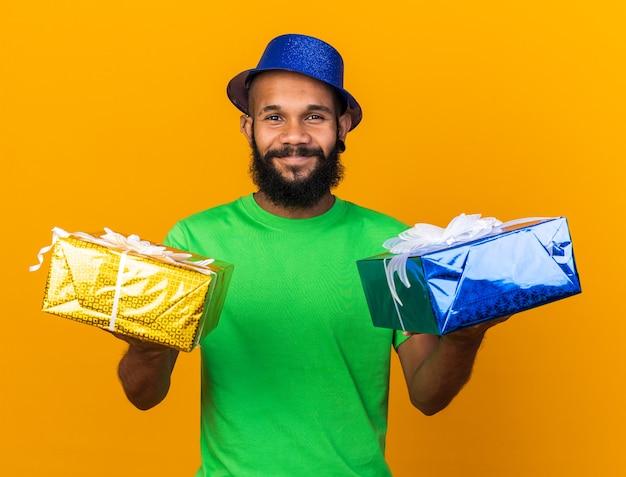 Uśmiechnięty młody afro-amerykański facet w imprezowym kapeluszu trzymającym pudełka na prezenty na pomarańczowej ścianie