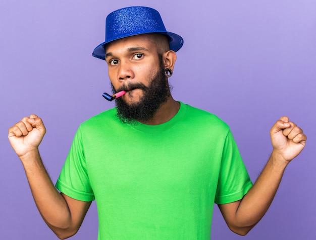 Uśmiechnięty młody afro-amerykański facet w kapeluszu imprezowym dmuchający gwizdek pokazujący gest