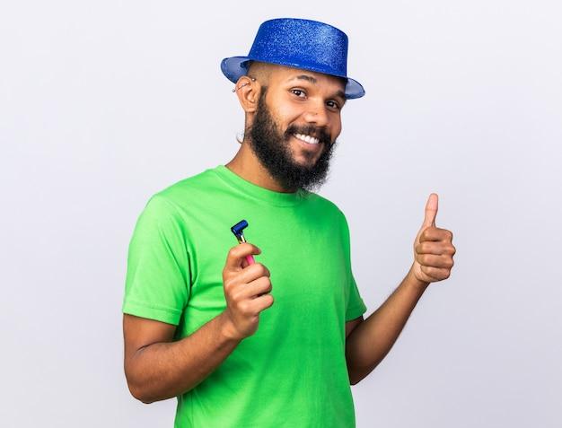 Uśmiechnięty młody afro-amerykański facet w kapeluszu imprezowym pokazując kciuk do góry, trzymając gwizdek na białym tle na białej ścianie
